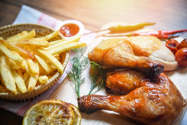 Жареные куриные ножки на деревянной разделочной доске и корзине с картофелем фри с кукурузой, лимоном, чили, пряными травами и специями
