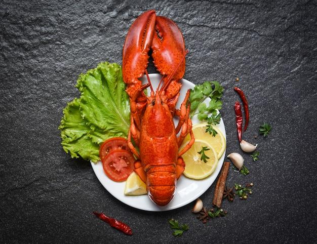Лобстер на тарелке из морепродуктов, моллюсков, креветок с салатом из лимона, салатом из овощей и помидоров