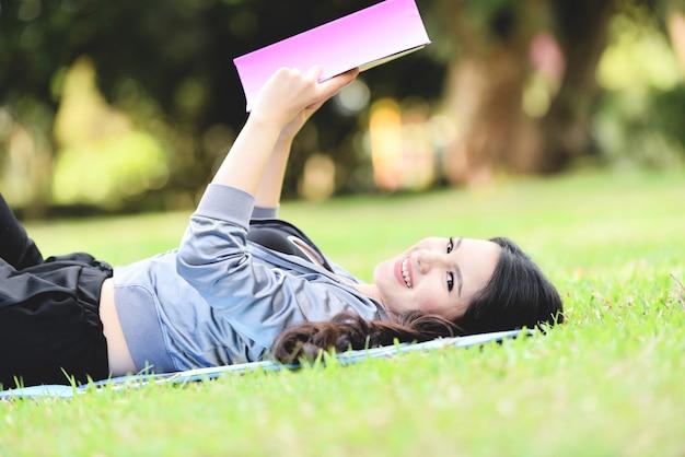 本を読んで、庭の公園で屋外の芝生のフィールドに横になっている若い女の子の笑顔幸せなアジア女性