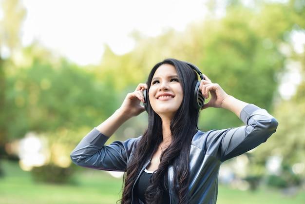 アジアの女性は屋外の携帯電話で音楽を聴く