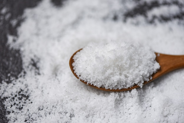 木のスプーンで塩と白い塩のヒープ