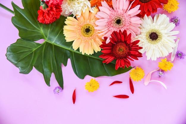 Свежие весенне-летние цветы обрамляют композицию из тропических растений герберы хризантемы