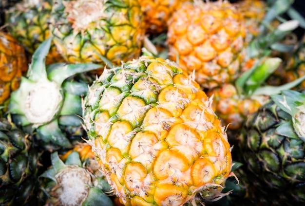 市場での販売のためのパイナップルガーデントロピカルフルーツから新鮮なパイナップル夏テクスチャ背景収穫