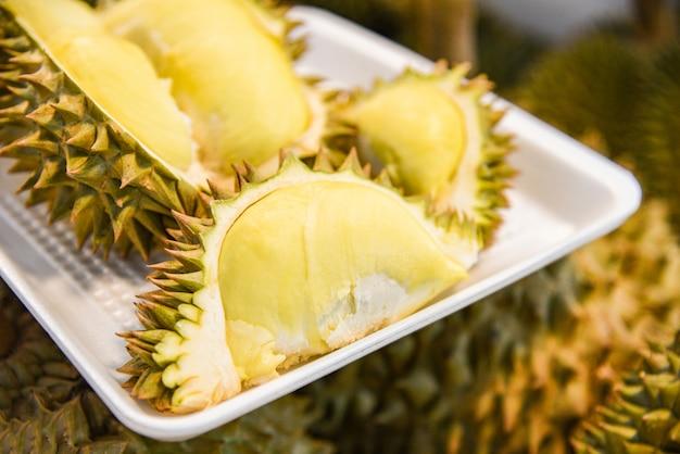 新鮮なドリアンのトレイと熟したドリアンの果実を市場での販売のための背景に皮をむいた