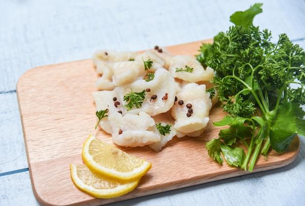 レモンと木製のまな板の上のスパイスと調理魚の切り身の部分