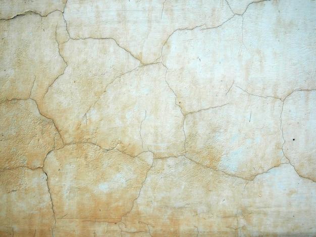 ひびの入った塗料で建物の古いセメントの壁