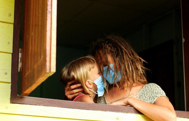 Мама и дочка в карантинной маске дома в изоляции