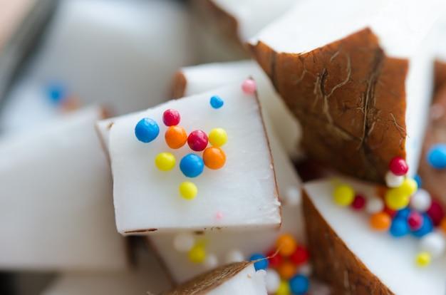 ココナッツキューブ、ボウルに色のキャンディーが入っています。マクロ写真。