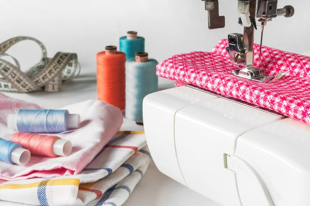 パステルカラーの背景、仕立て屋とデザイナーの机、手作りアクセサリー、スレッドロール、はさみ