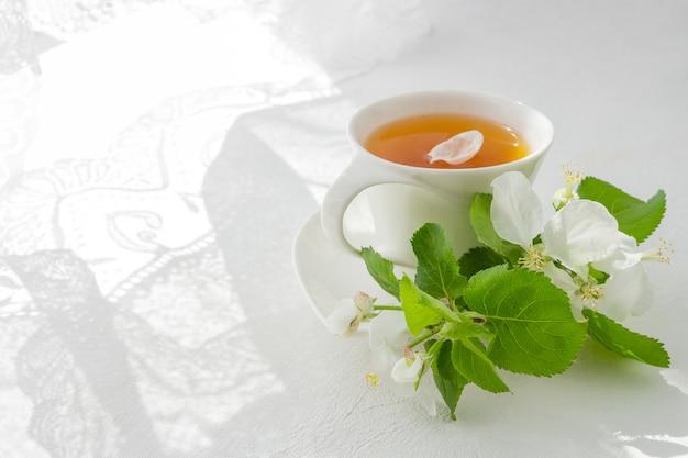 朝の窓の近くのライトテーブルとコピースペースを持つ花の束の上の紅茶のカップ