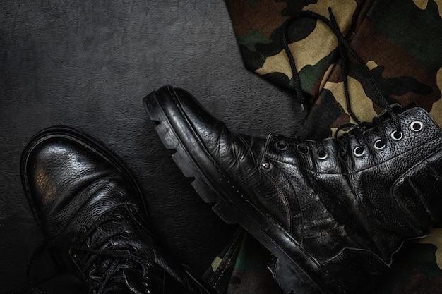 ミリタリー迷彩ユニフォームとブーツ。暗い背景に軍事アイテムフラスコ銃のセット