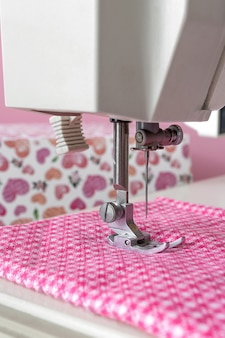 ミシン、コピースペースと明るい背景にセレクティブフォーカスとピンクの布の針のクローズアップ