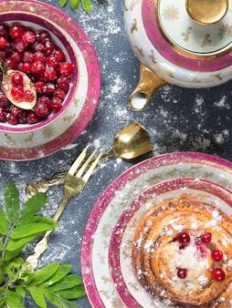 Стопка вкусных блинов с клюквой и вареньем на тарелку и салфетку на деревянном фоне
