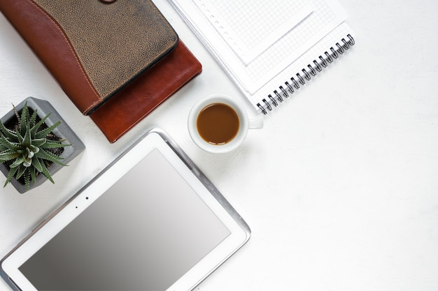 トップビューオフィステーブルデスク。空白のクリップボード、キーボード、事務用品、鉛筆、緑の葉のあるワークスペース