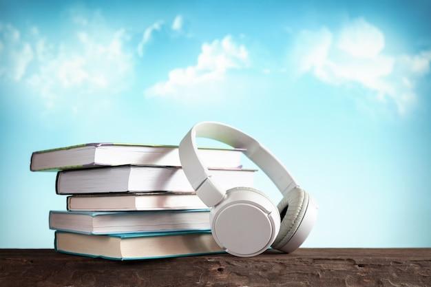 Белые наушники и книги, концептуальные книги, аудиокниги и электронное обучение, электронные книги