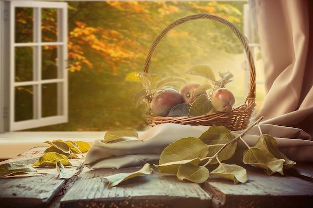 りんごバスケット、格子縞の本、秋の景色を見下ろす窓の近くのカップテーブル、秋