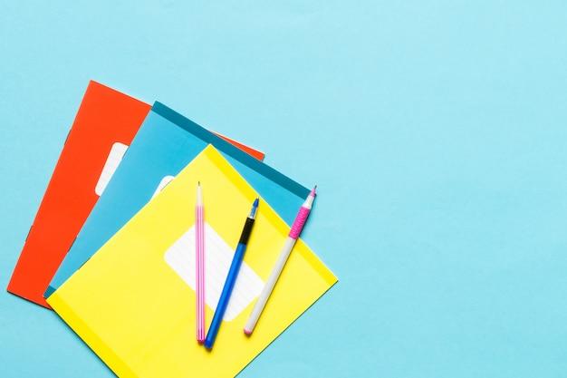 学校、ノート、ペン、青の背景に男子学生の職場の鉛筆用アクセサリー