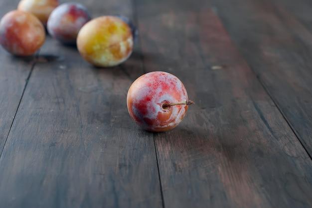 Свежие сливы от сада в шаре на старом деревянном столе.