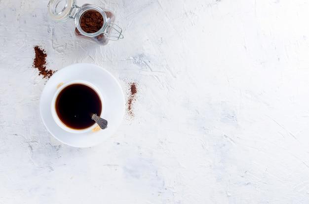 一杯のコーヒーとコーヒーの粉とガラス瓶