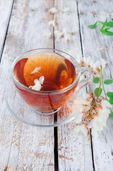 Чай из акации крупным планом на деревянных столах