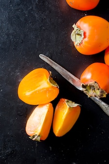 Спелая оранжевая хурма на черном