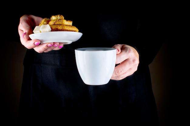 女性の手がカップとクッキーを握る