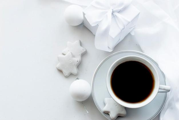Чашка с кофе, белая подарочная коробка, печенье и новогодние шары