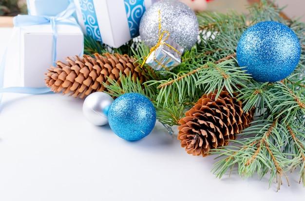 Новогодний фон с еловыми ветками, шишками, подарками, елочными игрушками