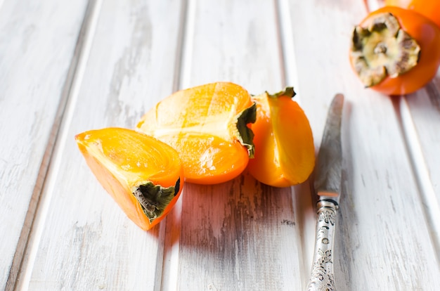 Спелые оранжевые хурмы на старый деревянный стол