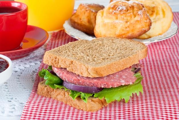 サンドイッチ、トースト、ジャム、ジュースと健康的な朝食