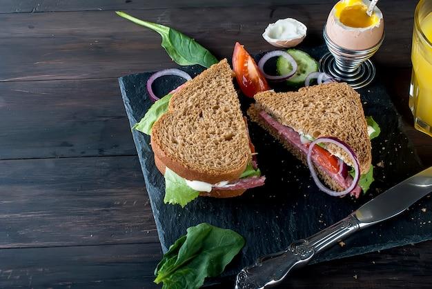 サンドイッチ、卵、カップコーヒー、朝食用ジュースのグラス