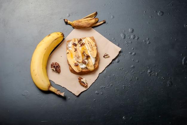 バナナ、ナッツ、チョコレート、黒いテーブルの上のおいしい甘いサンドイッチ