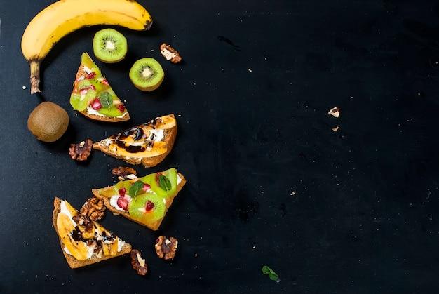 バナナ、ナッツ、チョコレート、キウイ、イチゴ、黒の背景にミントのおいしい甘いサンドイッチ