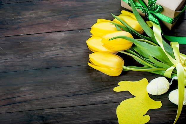 黄色のチューリップと木製の背景に青いリボンとチキンのイースターエッグの花束