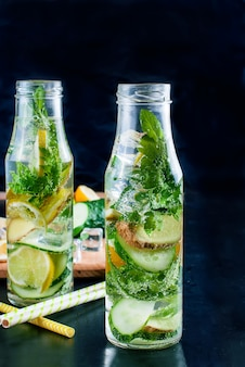 デトックスの新鮮な有機きゅうり、レモン、ミントの水のボトル