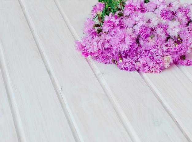 白い木製の背景にブーケガーデンヤグルマギク