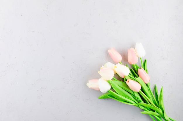灰色のコンクリートに明るいピンクのチューリップの花束