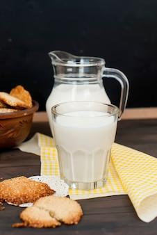 おいしいクッキーと素朴な木製のミルクのガラス