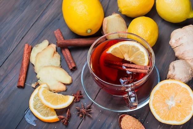 Чашка имбирного чая с лимоном и медом на темно-коричневом деревянном