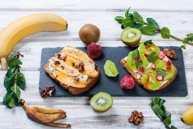 木製のテーブルにバナナ、ナッツ、チョコレート、キウイ、イチゴ、ミントのおいしい甘いサンドイッチ