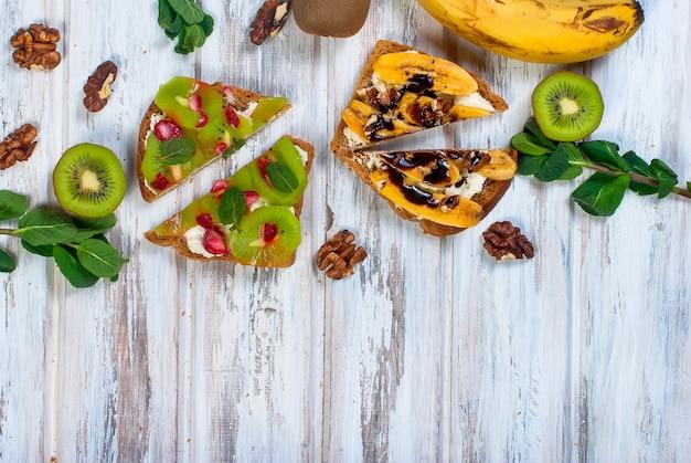 木製のテーブルにバナナ、ナッツ、チョコレートのおいしい甘いサンドイッチ