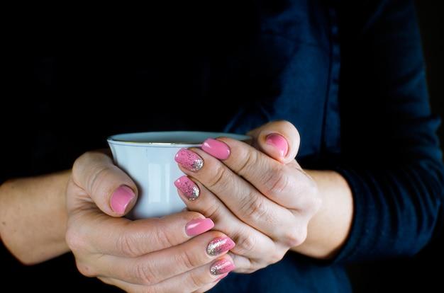 女性の手はカップを保持します