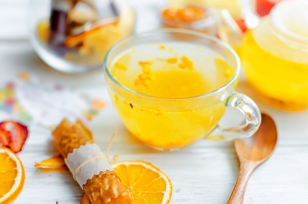 ガラスのカップとティーポットとフルーツのパスティーユの海クロウメモドキ茶