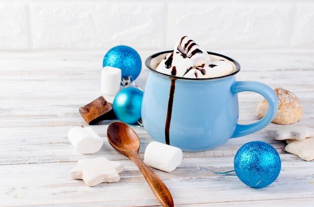 マシュマロと古い木製の背景に青いカップのチョコレートココア
