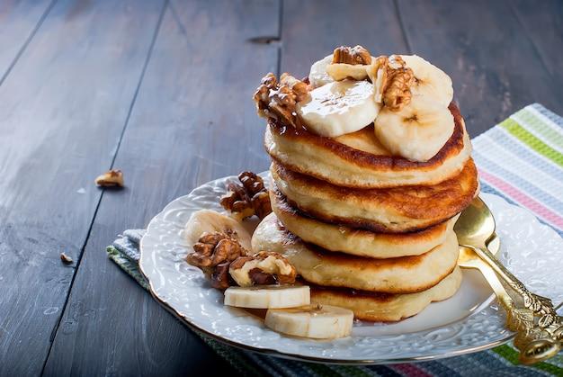 Блинчики с бананом, орехами, медом и чашкой кофе на темном