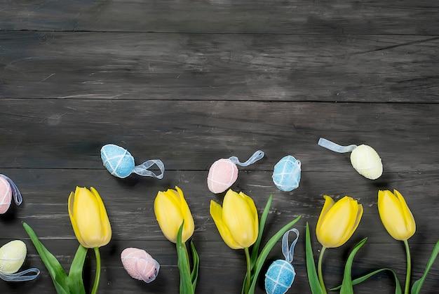 Букет из желтых тюльпанов и разноцветных пасхальных яиц на дереве