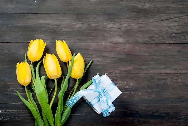 Букет из желтых тюльпанов и куриных пасхальных яиц с голубой лентой на дереве