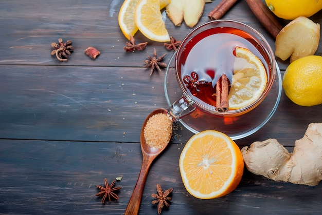 ダークブラウンの木製にレモンハチミツとジンジャーティーのカップ