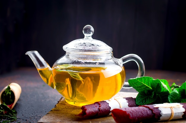 Горячий мятный чай в чайнике и сухой фруктовый кожаный рулет