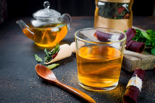 Чайная чашка, чай в ложке и сухофрукты